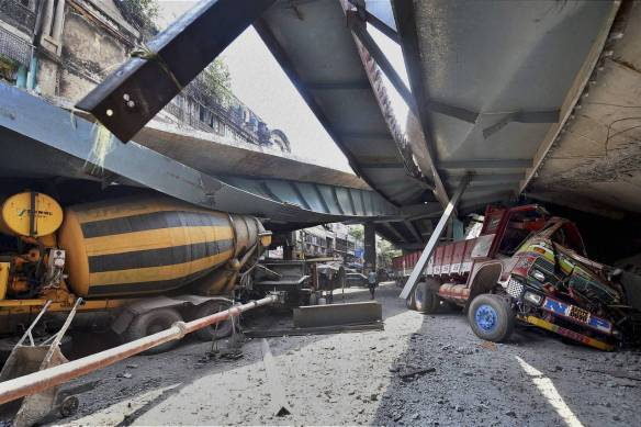 Vehicles are trapped under the partially collapsed overpass, which was being built over a congested road in a northern part of Kolkata.